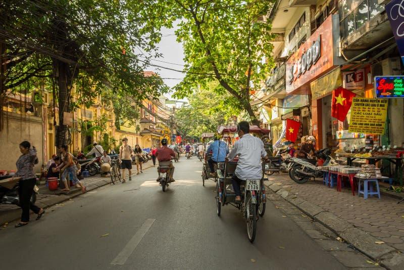 Rickshaw driver on busy street in Hanoi, Vietnam royalty free stock photos
