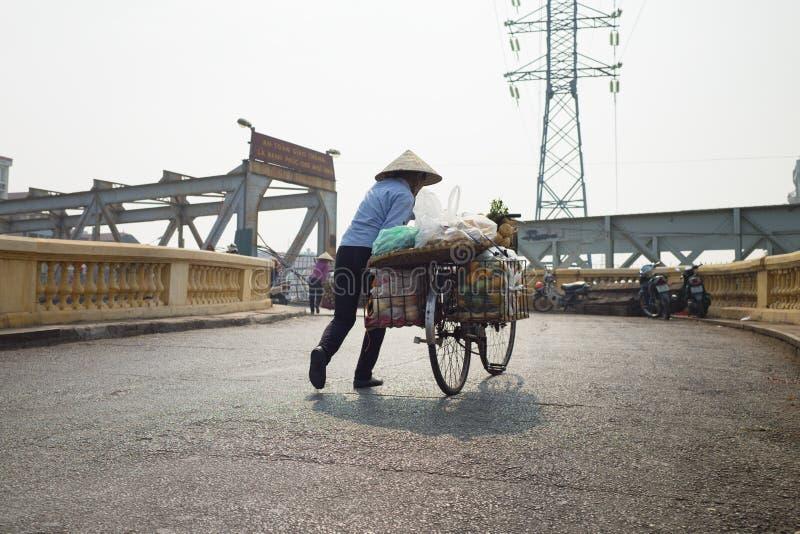 Hanoi Vietnam - Oktober 25, 2015: Kvinnaförsäljare som försöker att skjuta hennes frukt laddade cykel på den slarviga gatan på de royaltyfri foto