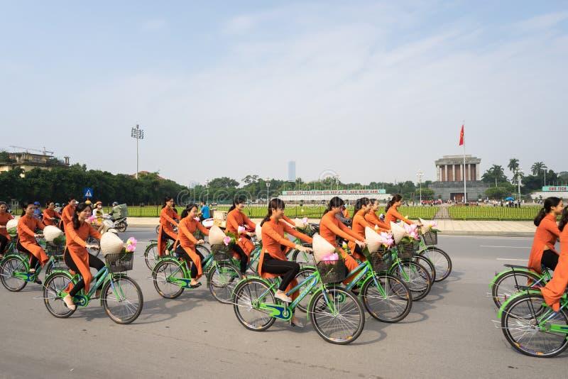 Hanoi, Vietnam - 16 ottobre 2016: Le ragazze vietnamite portano il vestito lungo tradizionale il Ao DAI che cicla sulla via di Ha immagine stock
