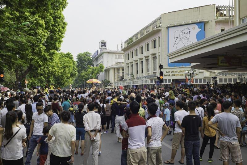 Hanoi, Vietnam - 2 Sep, 2015: Overvolle mensen die op kruising door Hoan Kiem meer op militaire parade op Nationale Dag letten royalty-vrije stock fotografie
