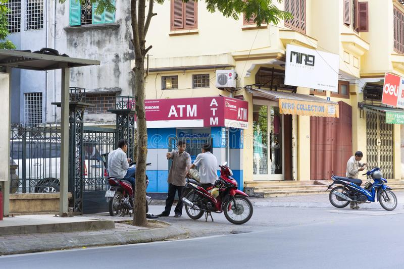 Hanoi, Vietnam - Sep 14, 2014: Unidentified group of taxi motorbike driver talking in front of ATM on Hoa Lu street.  royalty free stock image