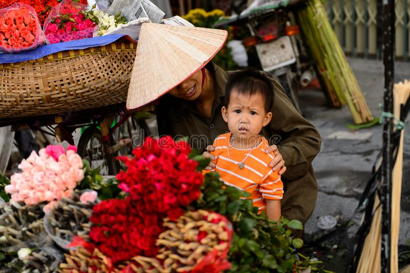 Flower market. HANOI, VIETNAM - SEP 23. 2014: Unidentified woman and her chlld works at the flower market in Hanoi, Vietnam. Flower market in Hanoi is one of the stock photo