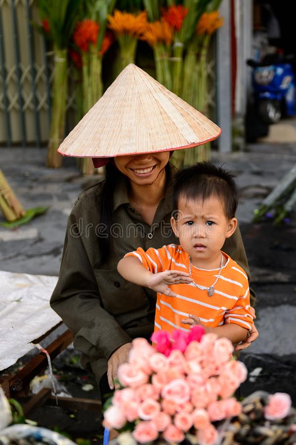 Flower market. HANOI, VIETNAM - SEP 23. 2014: Unidentified woman and her chlld works at the flower market in Hanoi, Vietnam. Flower market in Hanoi is one of the royalty free stock image
