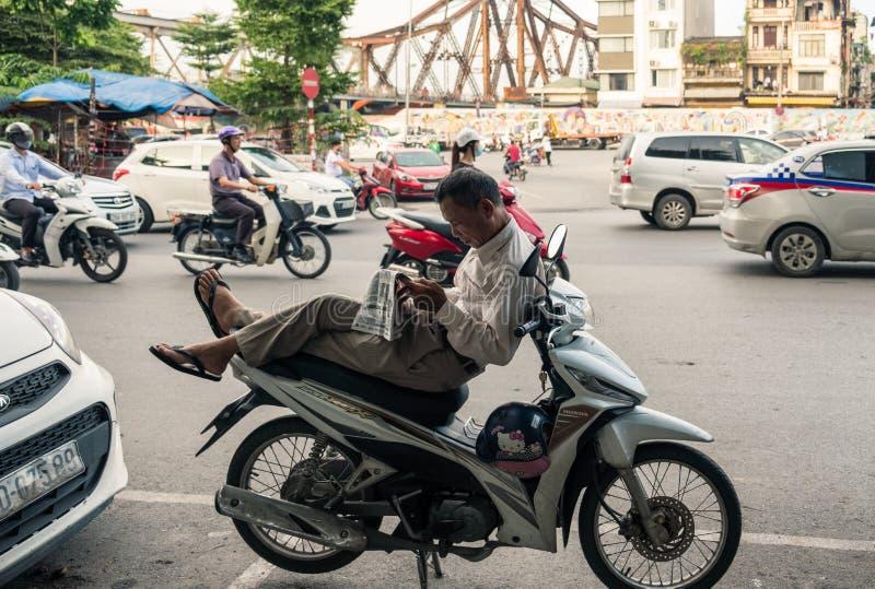 Hanoi, Vietnam - 10 Sep 2017: Vietnamese oomzitting op motorfiets met lezingskrant en opstopping royalty-vrije stock fotografie