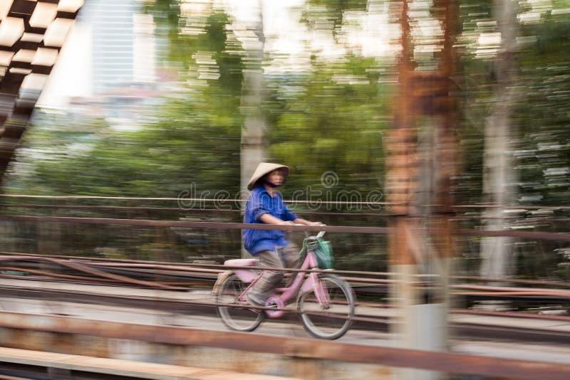 Hanoi, Vietnam - 10. September 2017: Vietnamesische Frau, die rosa Fahrrad auf langer Bian-Brücke radfährt lizenzfreie stockbilder