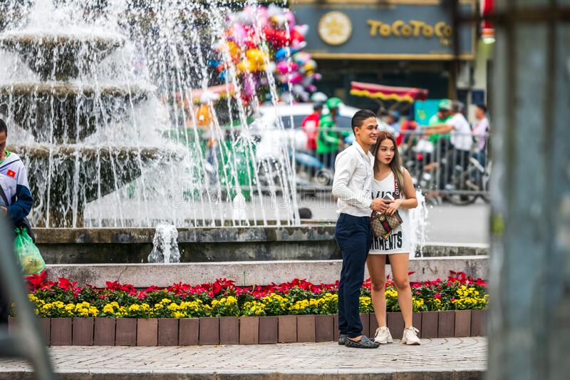 Hanoi, Vietnam - 11th October 2019: A young Asian couple taking photos next to a fountain in Hanoi, capital of Vietnam stock photo