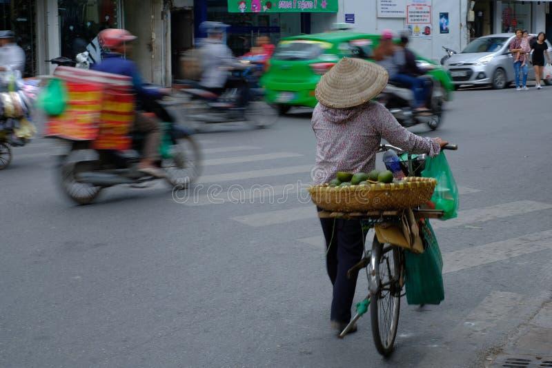 Hanoi/Vietnam, 05/11/2017: Vietnamese vrouw op fiets met traditionele rijsthoed op een bezige koortsachtige weg met het overgaan  royalty-vrije stock foto's