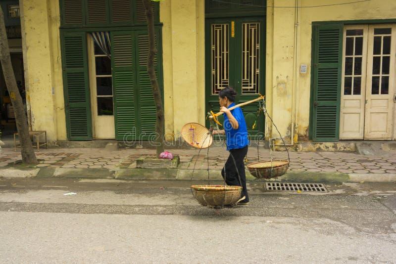 Hanoi, Vietname - 13 de abril de 2014: O vendedor não identificado vai em casa com as cestas vazias sobre a casa velha no estrept fotografia de stock