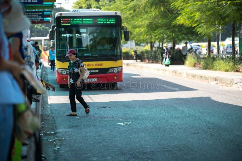 Hanoi, Vietname - 22 de agosto de 2017: Os povos estão andando através da estrada na frente do ônibus que vai parar na rua de Tra fotos de stock