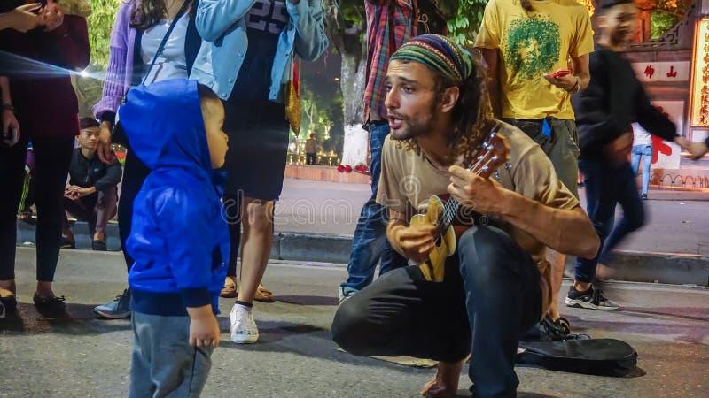 Hanoi, Vietname - 3 de dezembro de 2016: Guitarrista da rua que joga a música para uma jovem criança cercada por muitos povos foto de stock royalty free