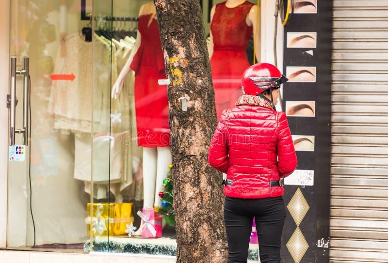 HANOI, VIETNAME - 16 DE DEZEMBRO DE 2016: Uma mulher em um revestimento vermelho no fundo das lojas Copie o espaço para o texto V imagens de stock
