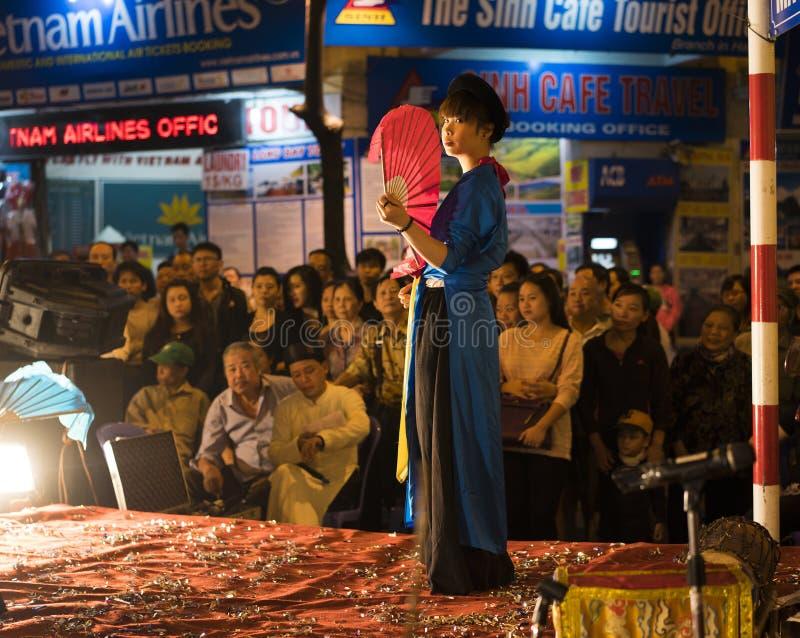 Hanoi, Vietname - 2 de novembro de 2014: O dançarino com fã vermelho e roupa tradicional velha executa a dança antiga da música f fotografia de stock royalty free