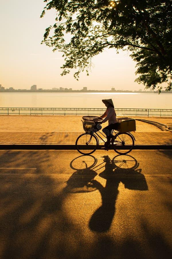 Hanoi, Wietnam - 28 Maj, 2013: Sprzedawca uliczny jedzie jej bicykl przez zmierzch przy Zachodnim jeziorem zdjęcie royalty free