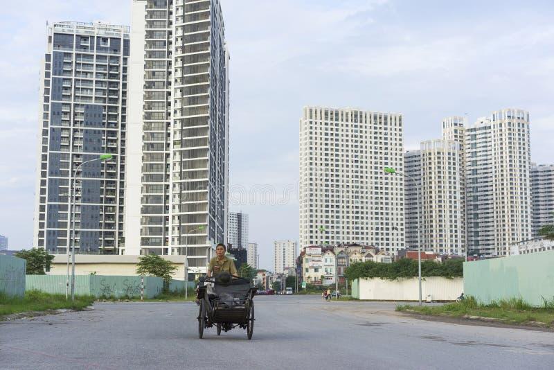 Hanoi, Wietnam - Sept 21, 2014: Niezidentyfikowany kobiety kolarstwo na obrzeże ulicie Hanoi miasto z wysokimi budynkami na tle, zdjęcia royalty free