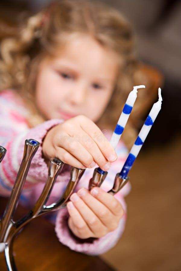 Hanoucca : La fille mignonne met des bougies dans Menorah photo stock
