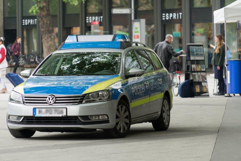 Hanover, Baixa Saxónia, Alemanha, o 19 de maio de 2018: Carro de polícia que está na borda da zona pedestre, agente da polícia qu fotos de stock royalty free