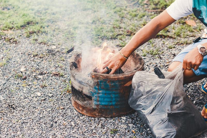 Hans man Fill charcoal briquette to hot flaming charcoal in bbq grill stove. Burning charcoal for cooking barbecue food. Fill charcoal briquette to hot flaming royalty free stock photos