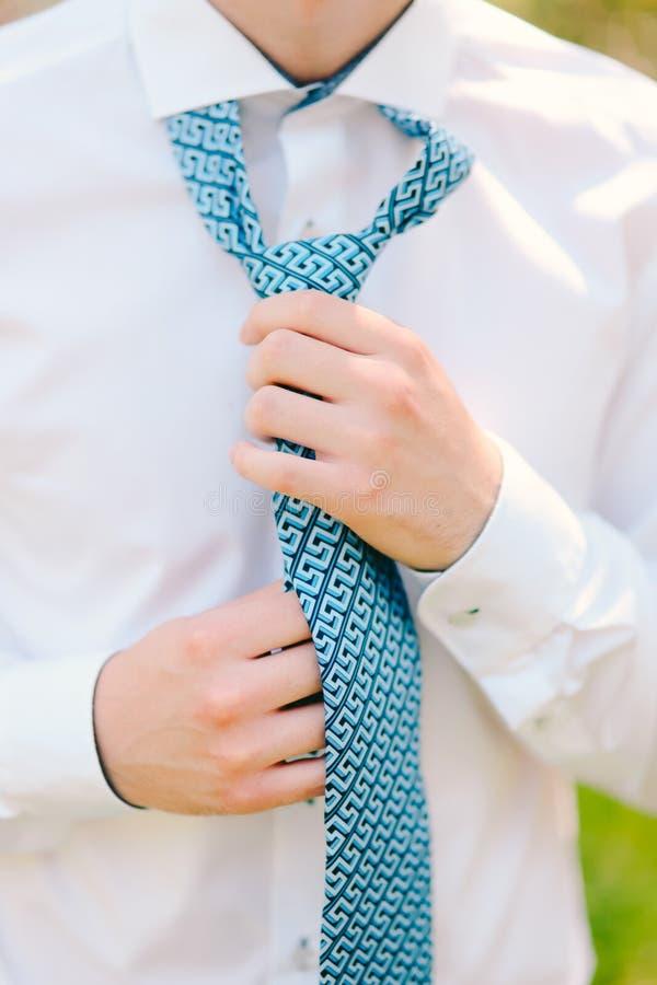 hans mantieband Brudgummen som binder hans band Gifta sig brudgumtillträde royaltyfria bilder
