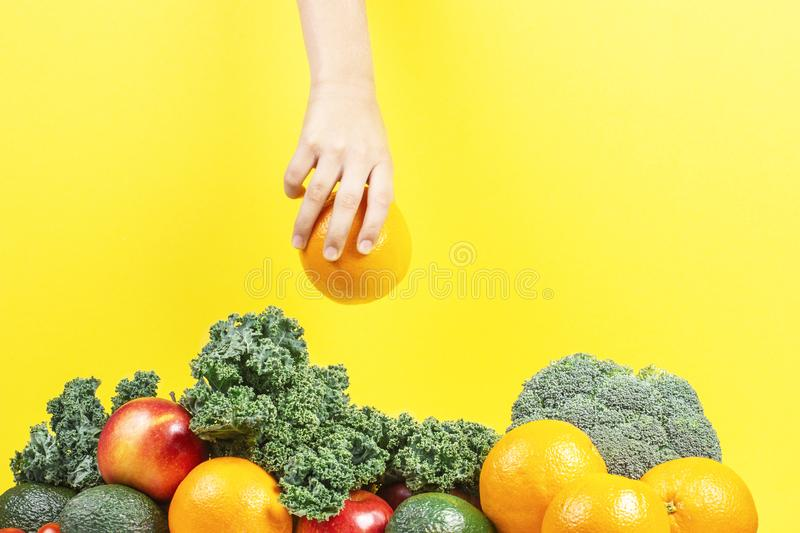 Hans picking one orange fruit from pile of fresh vegetables and fruits royalty free stock image