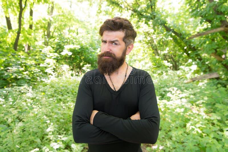 Hans sk?ggstil ser utm?rkt Brutal hipster som bär den trendiga mustaschen och att uppsöka hårstil Skäggig man som håller armar royaltyfri fotografi