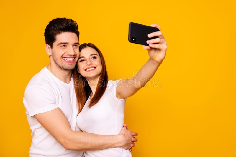 Hans stående av honom henne henne två trevliga attraktiva älskvärda gladlynta glade positiva personer som gör att ta selfie som f arkivbilder