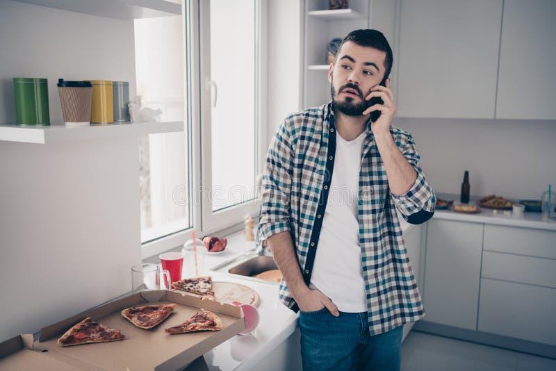 Hans stående av honom trevlig attraktiv ledsen trött uttråkad skäggig grabb som talar på telefonoperatör i modern ljus vit inre royaltyfri fotografi