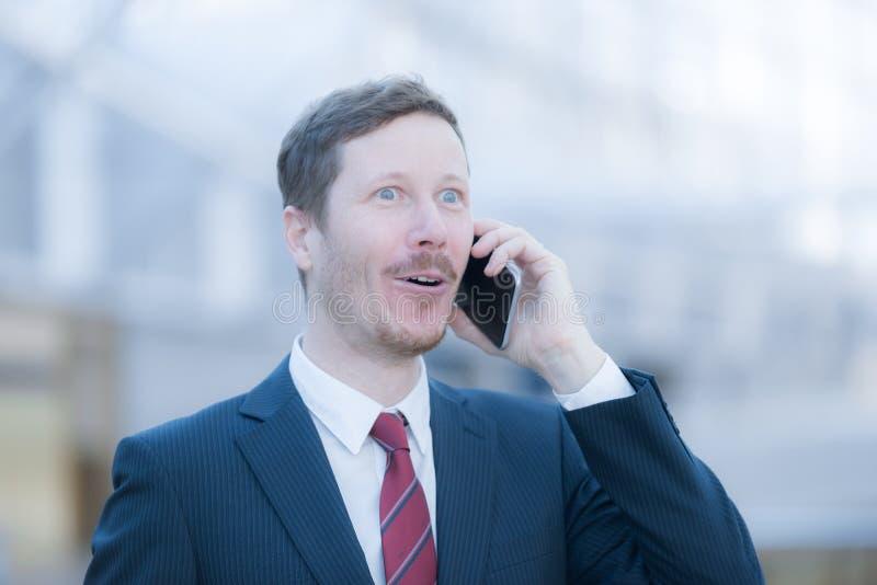 Hansdome mężczyzna na telefonie jest szczęśliwego i przesłuchania dobre'em wieści zdjęcie royalty free