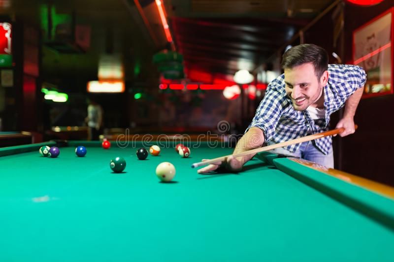 Hansome man playing pool in bar alone. Aiming royalty free stock photo