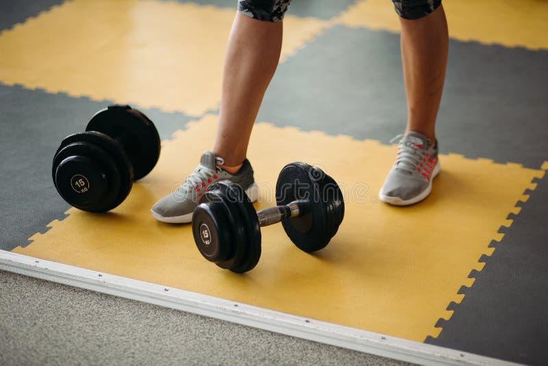 Hantel för konditionutrustning två nära kvinnlig fot på gult och svart golv i modern idrottshall arkivfoto