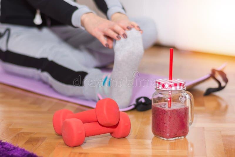 Hantel och smoothie i retro krus på golv och kvinnan som arbetar sträcka övningsben arkivfoton
