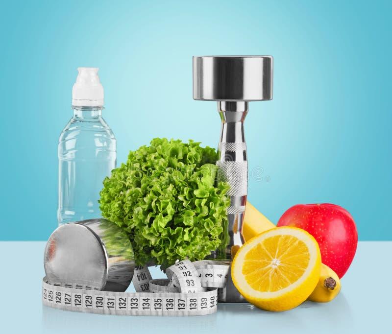 Hantlar med att mäta bandet, grönsaker och royaltyfri foto