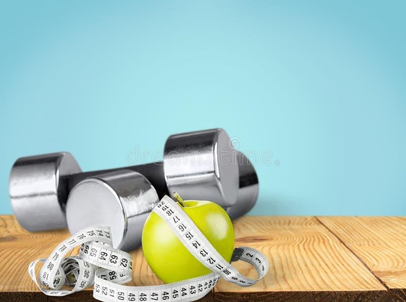 Hantlar med att mäta bandet och äpplet för bantar royaltyfria foton