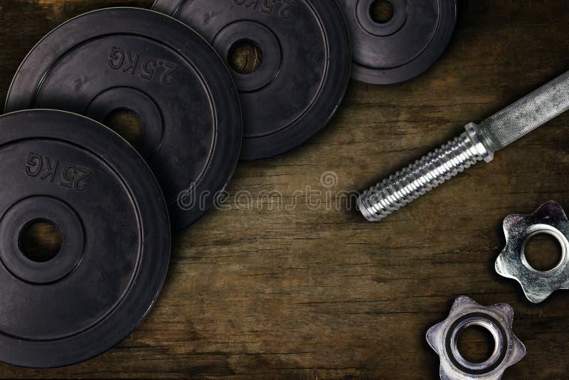 Hantlar och vikter ligger på golvet i idrottshallen Skivstånguppsättning och idrottshallutrustning Metallpåfyllningar i kondition fotografering för bildbyråer