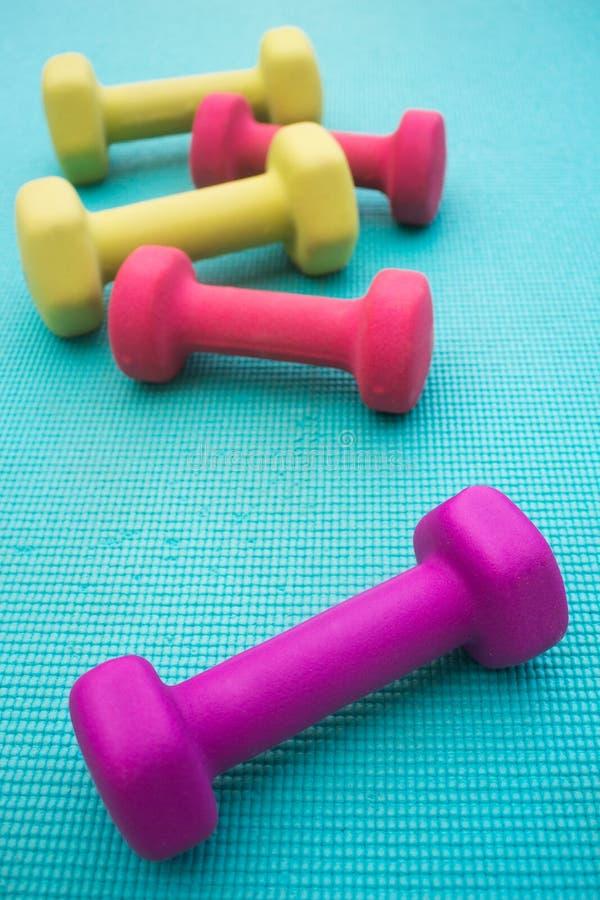 Hantlar på en matt yoga arkivfoton