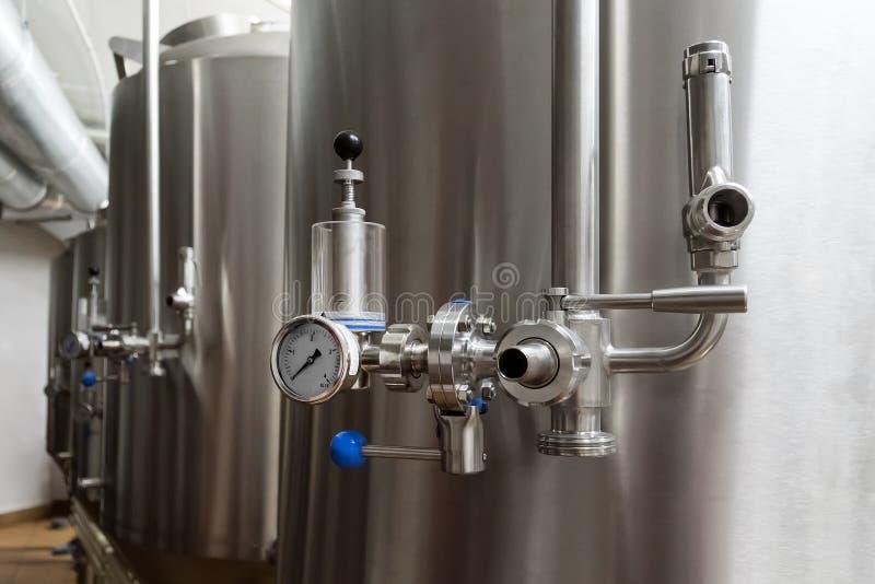 Hantverköl som bryggar utrustning i bryggeri Metallbehållare, alkoholdryckproduktion Lättheter i modern inre av bryggeriet Manufa royaltyfria bilder