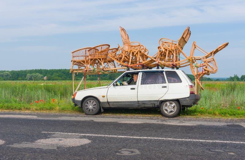 Hantverkare som har ett kort avbrott medan transportgnäggande-arbete på ett tak av en liten bil royaltyfria foton