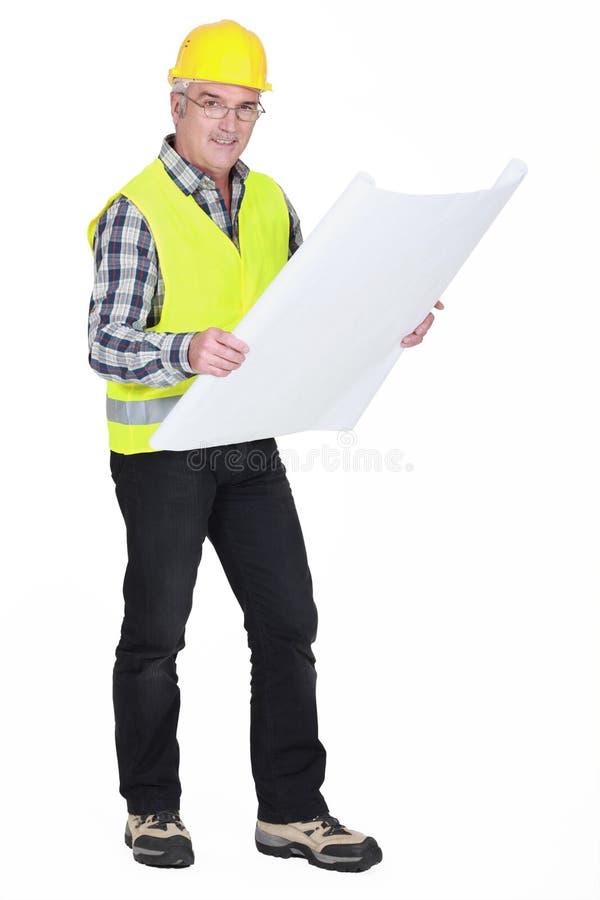 Hantverkare som rymmer en ritning arkivfoton