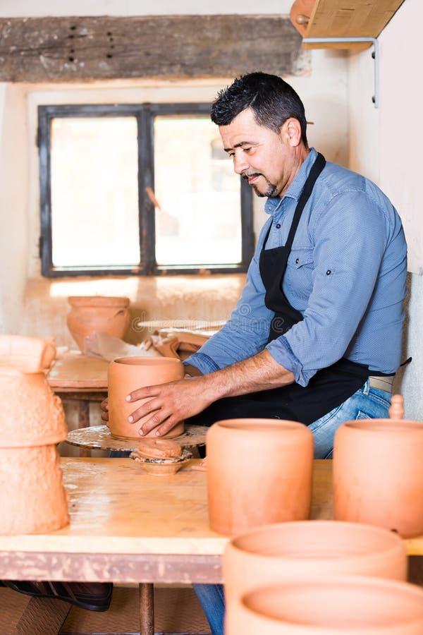 Hantverkaremannen som skapar det keramiska stycket på snurrkrukmakeri, rullar in royaltyfri bild