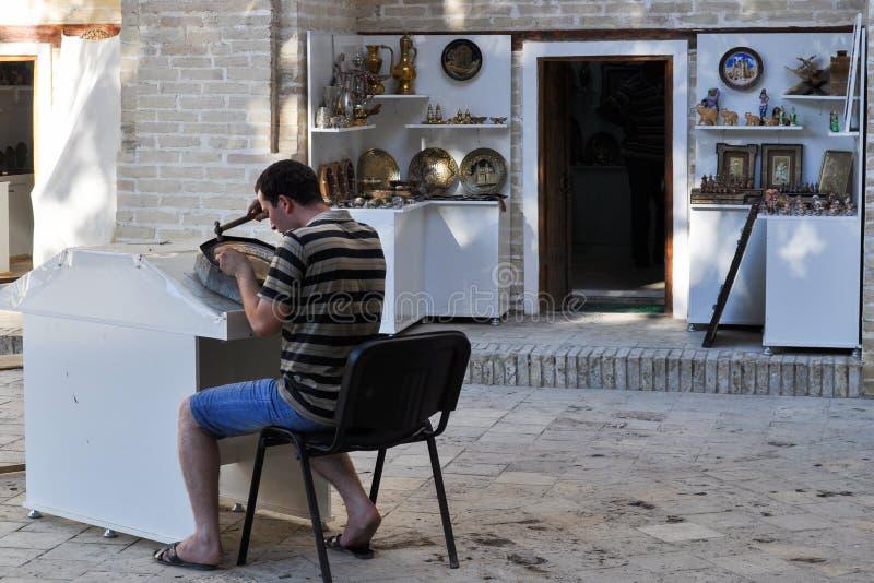 Hantverkaren arbetar i ett lager i Bukhara arkivbilder