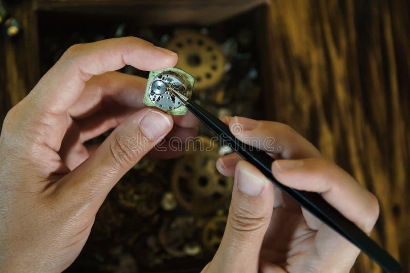 Hantverkaren demonterar klockor på brun bakgrund royaltyfri bild