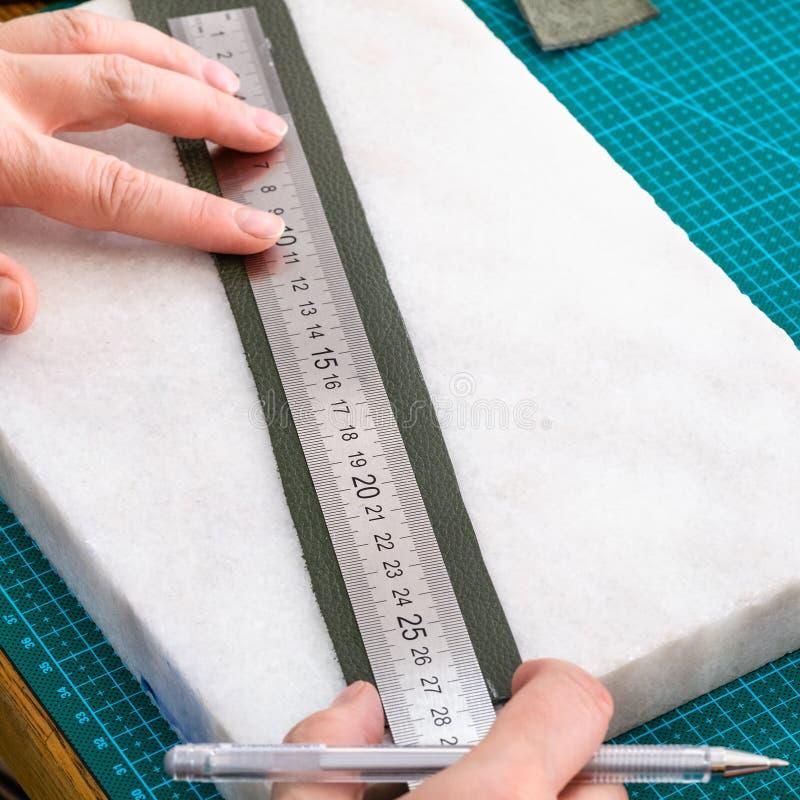 Hantverkaren drar modellen på bältemellanrumet för påse royaltyfri fotografi