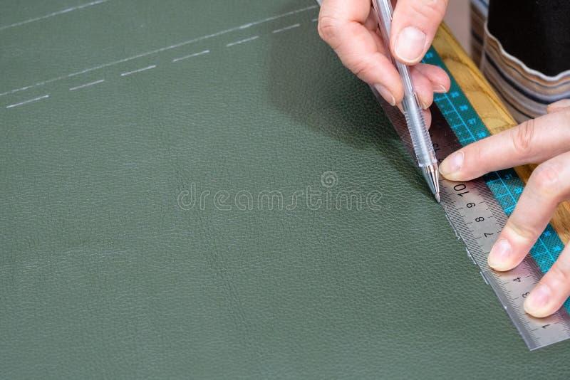 Hantverkaren drar modellen på läder genom att använda ruller arkivbilder