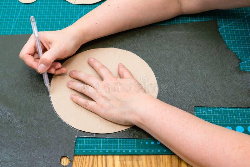 Hantverkaren drar skissar genom att använda pappersmodellen arkivfoto