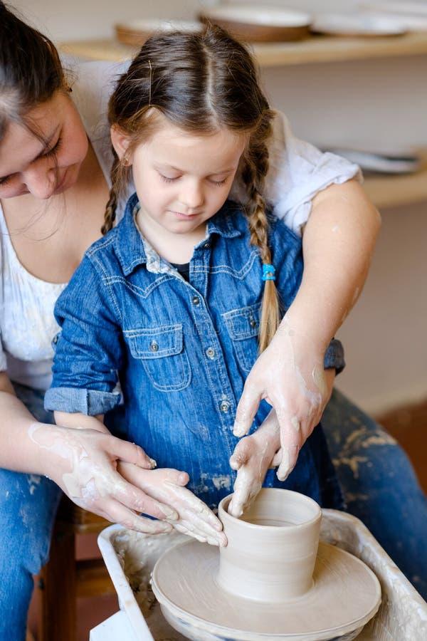 Hantverkaren för krukmakeriseminariumhantverket undervisar barnlera arkivbild