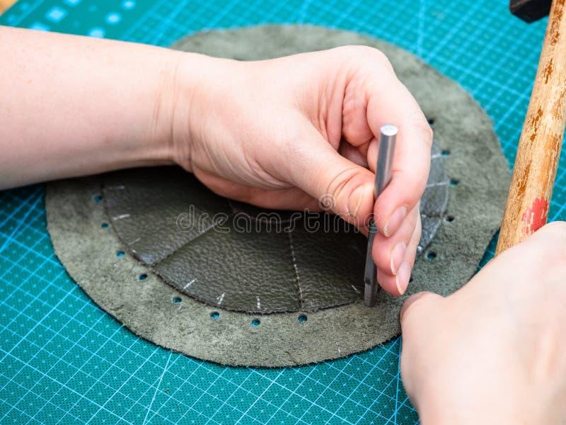 Hantverkaren gör perforering i den sydde påsen royaltyfri bild