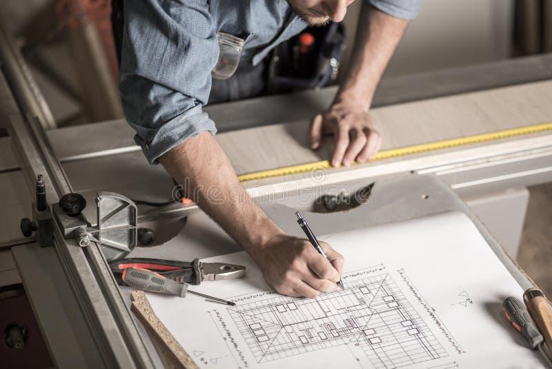 Hantverkares händer på arbetsbänken arkivbilder