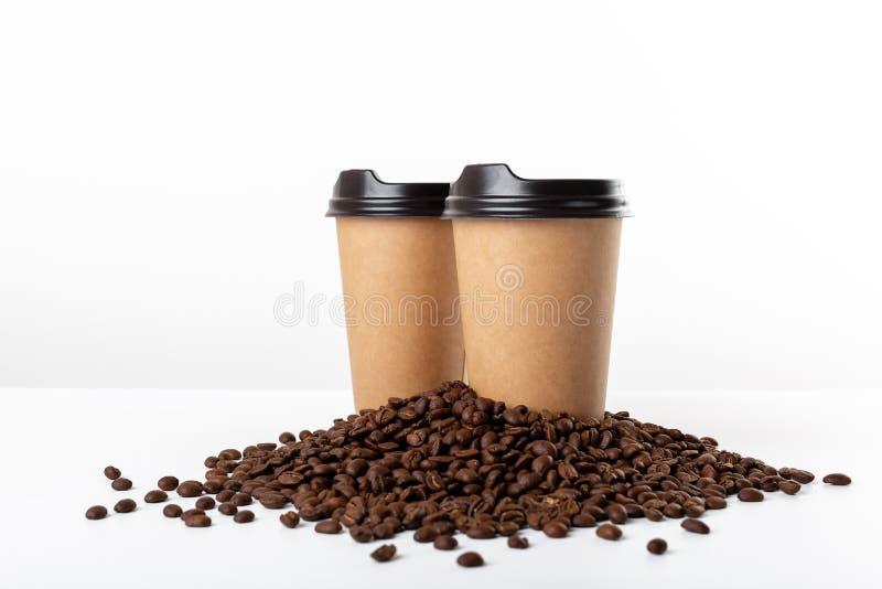 Hantverkkaffekoppar och kaffebönor på vit bakgrund fotografering för bildbyråer