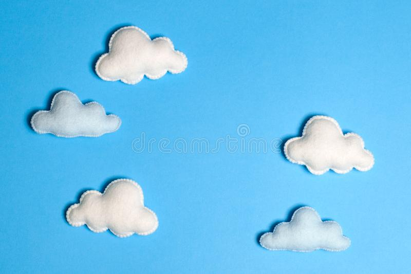 Hantverkvit fördunklar i blå himmel med ramen, copyspace Hand - gjorda filtleksaker abstrakt sky royaltyfri bild