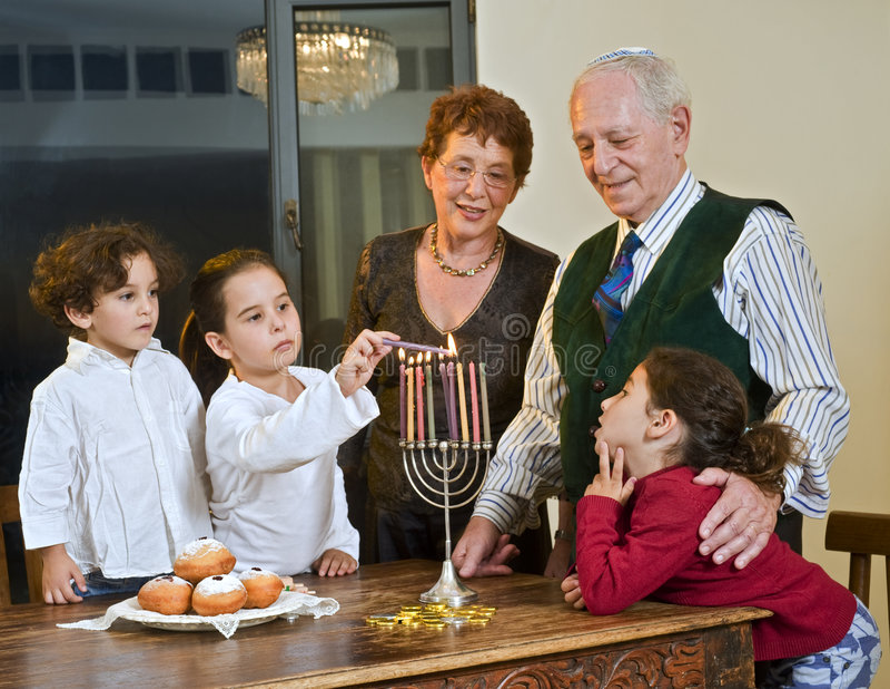 Hanukkah celebration. Grandparents and grandchildren lightening Menorah together
