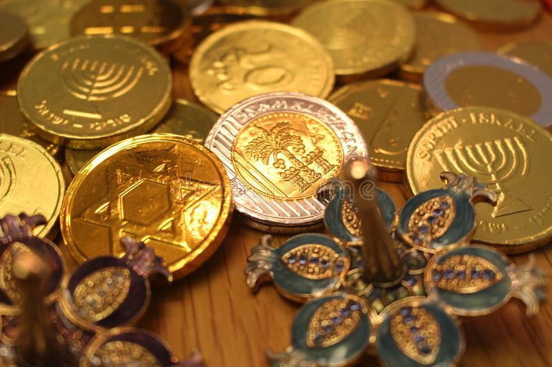 Hanukkah chocolate coins with star of David and menorah on back and silver dreidel with pomegranate royalty free stock image